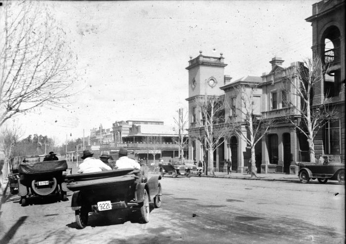 A car pulls out from the kerb in front of the Wagga Post Office in Fitzmaurice Street and heads off down towards the Johnston Street intersection, circa 1920s.